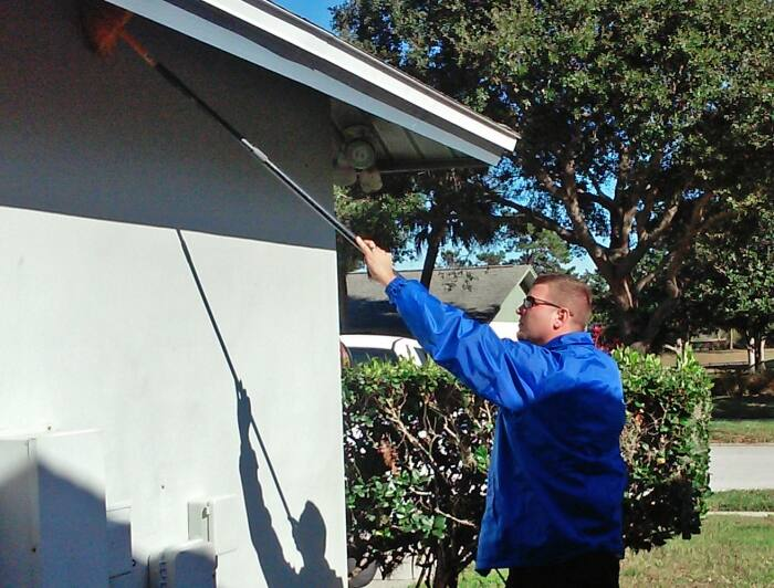 pest control technician spraying exterior of house